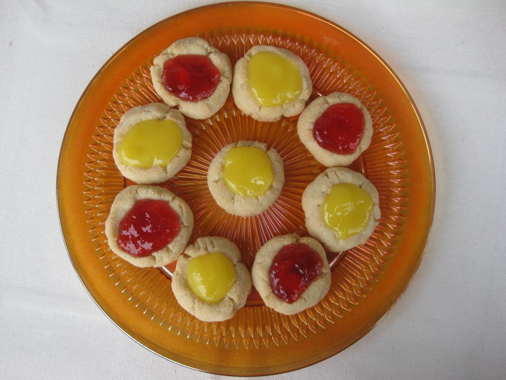 strawberry jam and lemon curd filled sugar cookies on an orange plate