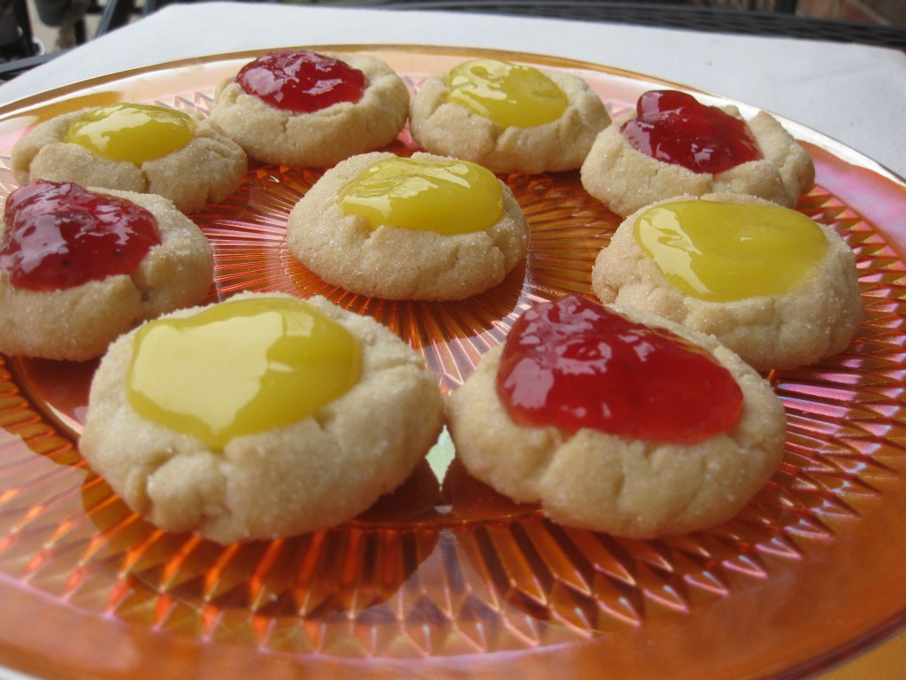 close up of lemon curd and strawberry jam filled sugar cookies on an orange plate